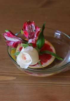 Floating Red Grapefruit Flower Arrangements  These simple flower arrangements add a splash of color to any winter tablescape. The red grapefruit slices suspend in the water for a unique centerpiece, and their rich, pinkish-red hue goes well with white, light pink and yellow flowers.