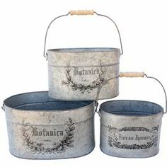 Set of three zinc buckets with typographic and laurel wreath designs.      Product:  Small, medium and large bucket          Construction Material:   Zinc        Color:   Gray and black           Features:   Stenciled design              Dimensions:       Small: 5.7 H  x 8.25 W x 5.5 D    Medium: 6.1 H x 10.2 W x 6.6 D    Large: 6.5 H x 12.2 W x 7.7 D                  Cleaning and Care:   Dust with a soft dry cloth