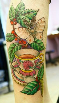 This tattoo design uses a tea cup, a moth and a tree branch to commemorate a deceased loved one