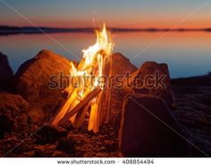 Stock Photo: Fire and flames of atmospheric campfire on the beach at night. Still water of the lake on the background with warm colors of sunset. Very shallow dept of field.