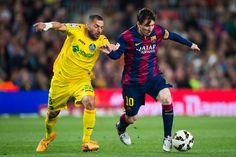 Lionel Messi of FC Barcelona competes for the ball with Mehdi Lacen of Getafe CF during the La Liga match between FC Barcelona and Getafe CF at Camp Nou on April 28, 2015 in Barcelona, Catalonia.