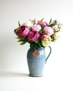 Rustic arrangement with peonies in light pink and light green / pink and cabbage roses in dark pink and champagne arranged in a rustic blue jug.