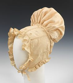 Sunbonnet ca. 1825, American (cotton)    Undoubtedly hand sewn at home, the exaggerated shape of this bonnet marks it as a highly fashionable example of the period. The back puff mirrors the puffed sleeves that were then fashionable. The rick-rack like openwork joining the sections is another notable feature.