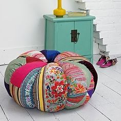 Colorful ottoman.  Someone has a time machine and went back to a college campus in the 60's and got this.