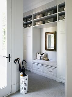 this classic country mudroom comes equipped with a small built-in bench and supersized storage closets.