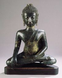 a north thai, ayutthaya style, bronze figure of buddha sakyamuni 16th century Seated in virasana with his right hand in bhumisparshamudra while his left rests on his lap, wearing samghati leaving his right shoulder bare, his face with meditative expression, arched eyebrows above incised eyes, aquiline nose, smiling lips, elongated earlobes, curled hairdress and usnisha 62 cm high, on wood base