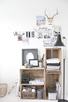 i love everything about this display. the collage wall display, the antlers, the old wooden boxes repurposed to make shelving, the black & white color scheme...