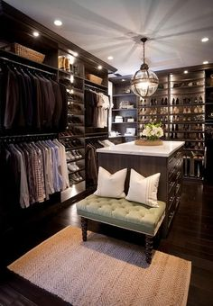 Custom walk-in closet features dark stained built-ins boasting shelves over stacked clothes rails flanking sloped shoe shelves accented with custom lighting.