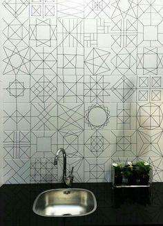 Azulejos blancos con figuras geométricas en negro, usado en cocina. Buena elección en colores y mucho mejor elección, al colocarlos en la cocina que además de ser fácil de limpiar, le dan movimiento y diseño al espacio tan cotidiano.