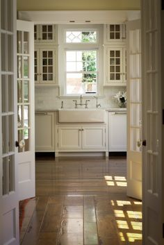 white cabinetry, french doors, farmhouse sink and wide planked wood floors