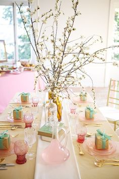 Pink depression glass table setting, gold flatware, turquoise ribbon, gold paper, flowering branches, fabric cloth and runner, old books, glass decanter, glass bottles