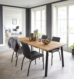 Elegant grey-toned dining room, with wide windows letting light shine in and a cosy feeling from candles and skin.