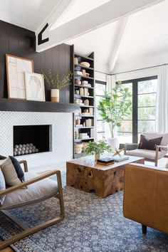 Neutral Living Room Design + Tribal Decor + Wood Coffee Table + Leather Couch + Shiplap Fireplace + Diamond Pattern Tile + Black + Navy Rug + Modern Chairs + Black Pane Windows + Trussed Ceiling + Open Wood Beam Ceiling + Built-In Storage Home Living Room, Living Room Designs, Living Room Decor, Neutral Living Rooms, Living Room Ideas, Style At Home, Br House, Design Salon, Tribal Decor