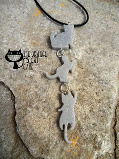 Hand cast glittery resin climbing cats necklace and hung on a black leather cord.  Choose from a 1, 2 or 3 cat necklace! Choose the colour of the cats!  The charms are hand cast using high grade jewellery resin. Resin is a great alternative to glass, it is scratch resistant and can withstand being dropped or knocked about.  All my resin pieces are hand cast and as a result may contain small bubbles, this is not a fault, rather the result of not being factory made. Each piece takes me 3-4…