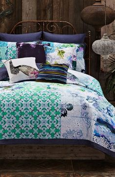 Adore the mix of patterns and textures on this pretty teal and purple bed collection.