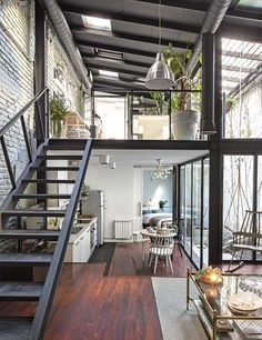 industrial style apartment with exposed steels painted black, painted brick and wooden flooring