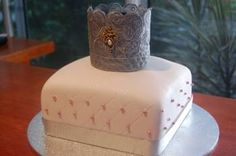 Charlie Girls's Princess/Tiara cake. Took inspiration from many of the cakes I pinned. Stiffened Lace Tiara also made from an idea on Pinterest. Vanilla buttercake, covered with buttercream and baby pink fondant, quilted on edges with a tracing wheel, dotted with edible pink pearls, and dusted with edible sparkle dust. First attempt at fondant!