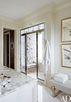 Shower fittings by Michael S. Smith for Kallista are used in the master bath, which features boldly veined marble surfaces.