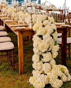 Trending now - flowers(here it's white hydrangea0  arranged like a table runner cascade onto the floor. Very nice touch.