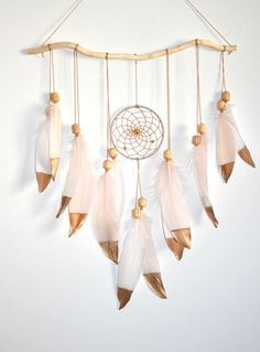 Lovely handmade wall hanging dream catcher adds a little boho to any living space. New baby? Bridal shower? Makes a thoughtful gift to a Loved one or yourself.  Dream catcher Wall Hanging Details: -This boho wall hanging was made with a beautiful piece of wood stick, little dream catcher, large blush and snow white natural feathers, wooden vintage beads. It has gold beads in the middle of a hoop. Natural goose feathers was hand painted in gold. Measures: Dreamcatcher ring 4 inches in…