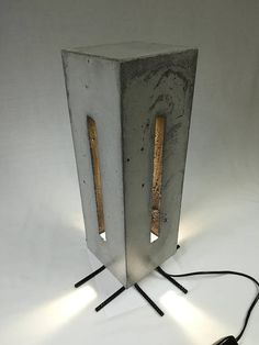 Name: Elemental A statement lamp made from steel reinforced concrete. Made over a period of 2 months, this bespoke handcrafted item is made to order. Specifications: -Material: concrete, reinforcing steel, -Height = 49 cm -Depth = 15.5 cm -Width = 15.5 cm -Weight = 17.15 kg Extremely long life LED (GU10) Bulb Warm White 3000K (35W equivalent) 15,000hrs. Black In-line switch, UK Plug only.