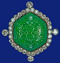 Emerald and diamond brooch Probably Garrards Presented to Queen Mary at the Delhi Durbar by the Ladies of India and inherited by The Queen in 1953. The large hexagonal emerald, in a gold and silver setting encircled by brilliant-cut diamonds, is carved with a rose on the front and a plant on the back.
