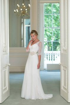 Naomi Neoh 'Violette' - a slim line corseted dress of soft tulle draped over light weight Chantilly lace with a hint of antique peach. The demure ¾ length sleeves and ribbon belt with a silk flower corsage complete this elegant gown.  www.naomineoh.com