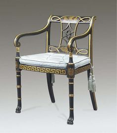 A REGENCY EBONISED AND PARCEL-GILT OPEN ARMCHAIR  EARLY 19TH CENTURY  The pierced toprail centred by a tablet decorated with figures before a sphinx above a pierced rope twist splat and winged lion's-head tablet, with downswept scrolled arms, a caned seat and buttoned squab cushion above a Greek-key seatrail, on ring-turned tapering legs headed by lion-masks and with paw feet.