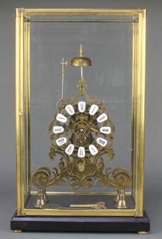 """Lot 761, A Victorian style fusee brass skeleton clock with enamelled numerals contained in a gilt and glass case 21"""" x 12"""" x 8"""", est £400-600"""