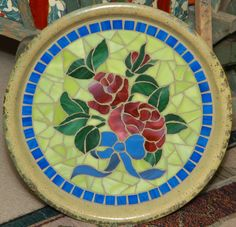Done on a planter saucer, using stained glass and glass mosaic tiles.