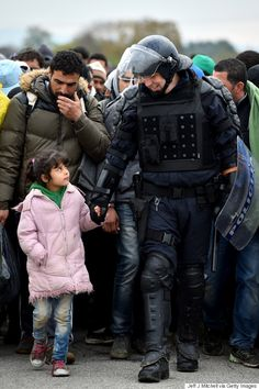 難民の少女は、警官と手をつなぎながら国境を渡った。自由を求めて(画像)