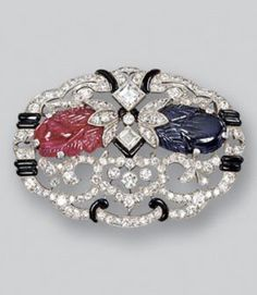 An Art Deco gem-set brooch, circa 1925. The oval openwork plaque of foliate inspiration set throughout with circular-cut diamonds, decorated with a carved ruby and a carved sapphire, highlighted by black enamel. #ArtDeco #brooch