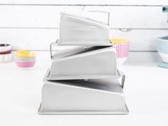 """Go mad for the Fat Daddio's Mad Dadder Square Cake Pan Set! Defy gravity and expectations with pans that bake sloped tops and sharp angles for perfectly stacked cakes. Your set arrives complete with pans measuring 10""""x4"""", 6""""x4"""" and 8""""x4"""" to 2.5"""", so you're ready for any crazy cake request that comes your way. Plus, Mad Dadder anodized aluminum pans have an exclusive STAYLEVEL stand that balances your batter in the oven for even baking and incredible results."""