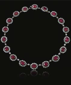 THE ESTATE OF CHRISTIAN, LADY HESKETH. Ruby and diamond necklace, Mid 19th Century. Designed as a series of graduated oval clusters, each set to the centre with an oval ruby within a cut-down collet surrounded by a border of similarly-set old-mine diamonds, length approximately 390mm, cased.
