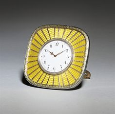 A silver-gilt and gold-mounted guilloché enamel sunburst clock, marked Fabergé, workmaster's mark of Michael Perchin, St. Petersburg, circa 1898, with scratched inventory number 57929.  Square with rounded corners, chased and engraved gilt laurel rim enclosing the sunburst yellow enamel with applied gold rays, emanating from the seed-pearl set bezel, marked on lower rim, strut and casing 3 5/8 in. (9.2 cm.) high.