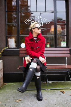red coat, black skirt, tights and boots with grey socks