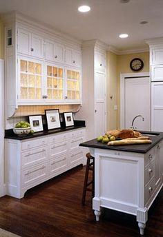 Love the black countertops, white cabinets, and the pale yellow walls. <3
