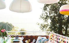 Un espacio exterior con telas de vivos colores, una zona para sentarse y una mesa de comedor con sillas.