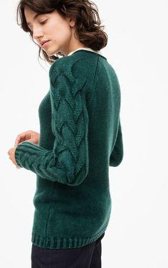 Der flachgestrickte Pullover ist schmal geschnitten und besticht durch das Zopfmuster welches entlang der Ärmel läuft. Der besondere Rundhalsabschluss und die l