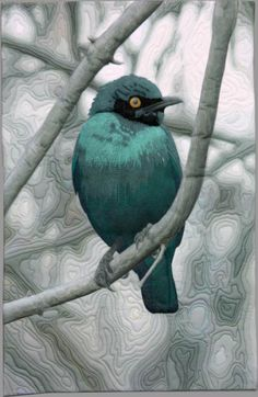A Greater Blue Eared Starling from Botswana is treated with embroidery and trapunto. An art quilt by Barbara Barrick McKie