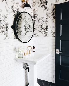 Beautiful black and white bathroom with a delicate floral wallpaper, round mirror, and pedestal sink.