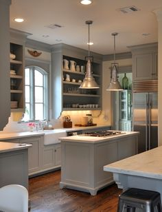 Gray cabinets, industrial lighting above cooktop island, open shelving.
