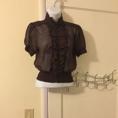 Bebe shirt Sheer brown shirt.  Ruffled elasticized bottom.  Row of shiny brown buttons. 20% off bundles of 2 or more ask about discounted shipping bebe Tops Blouses