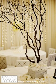 Manzanita tree with hang in crystals and white phales at the base. The all white background, tables and chairs really make the tree stand out! #whitewedding