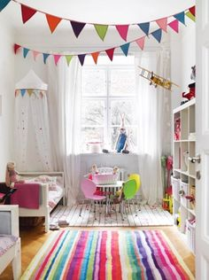 I love this color scheme - walls are neutral, but the art, rug, and furnishings bring a lot of fun colors into this kids room...