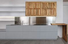 Sophisticated and harmonious interpenetration of volumes and natural materials.  Coplanar wall units in antique wood, Eco-Cement finish bases and peninsula with cantilevered worktop.