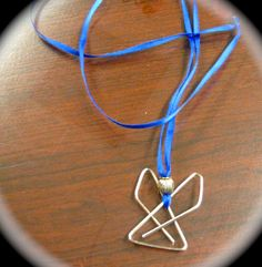 Make these cute angel necklaces with a large paper clip, a silver ball and ring, and some ribbon!