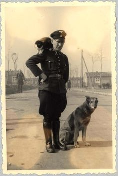 Esterwegen, Germany. A cat finding shelter from a dog on a policeman's shoulder.