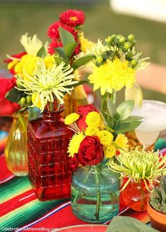 You'll love these tabletop and entertaining ideas for Cinco de Mayo - centerpiece of mixed flowers in bottles of various colors, sizes, and shapes