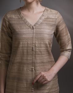 This tussar silk ghicha knee length kurta is a perfect for a smart day wear as well as an elegant evening wear. Coordinate this kurta with our tussar cotton pants for a casual look. The V neck with pintucks and loop buttons lends it a rich look. Tussar Silk Ghicha V Neck Pintuck 3Q Sleeves Dry Clean Only